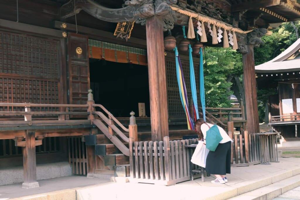 Girl bowing at Hachiman shrine