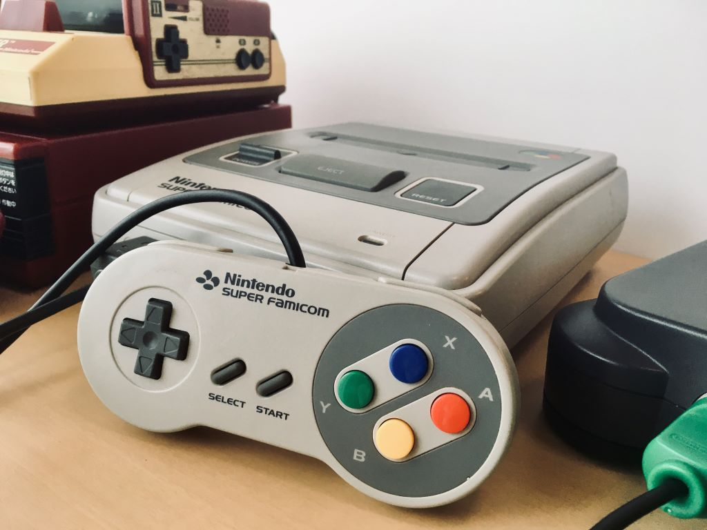 The Super Famicom, the Japanese equivalent of the Super Nintendo Entertainment System, between a Famicom atop a Famicom Disk System (left) and a Nintendo 64 (right)