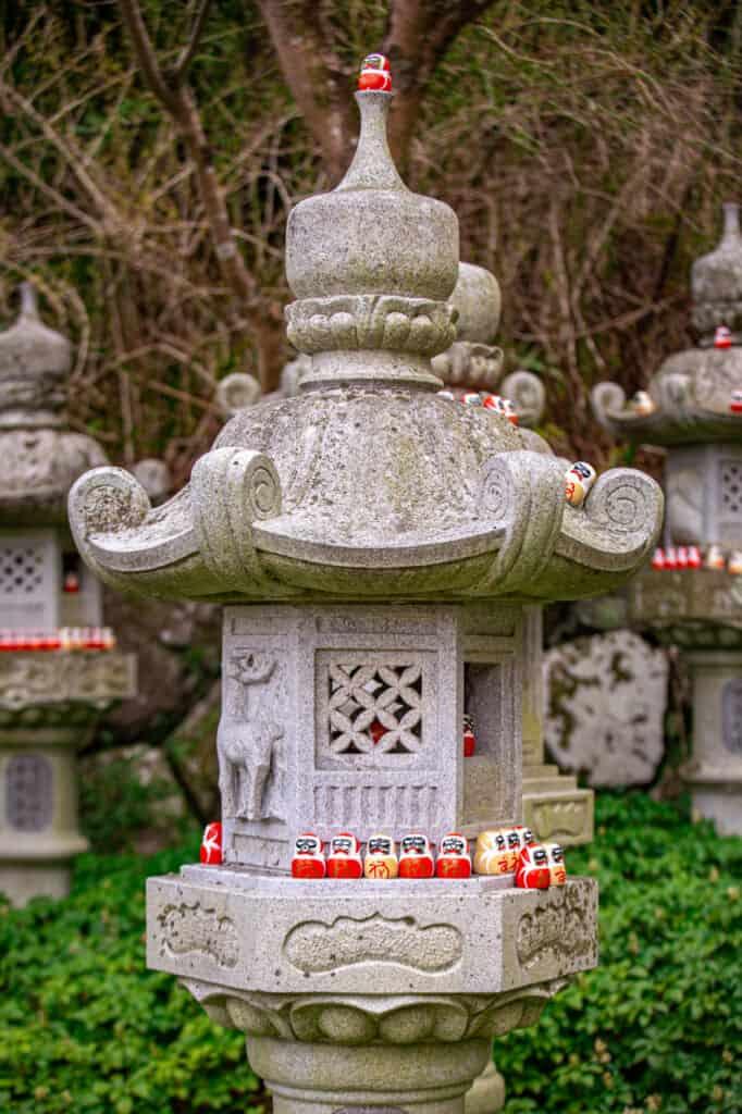 daruma in a stone lantern in katsuo ji temple
