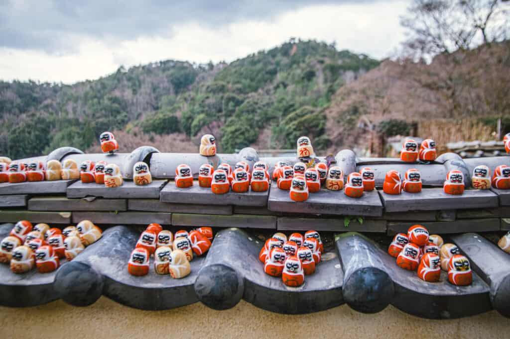 dozens of small daruma on a roof
