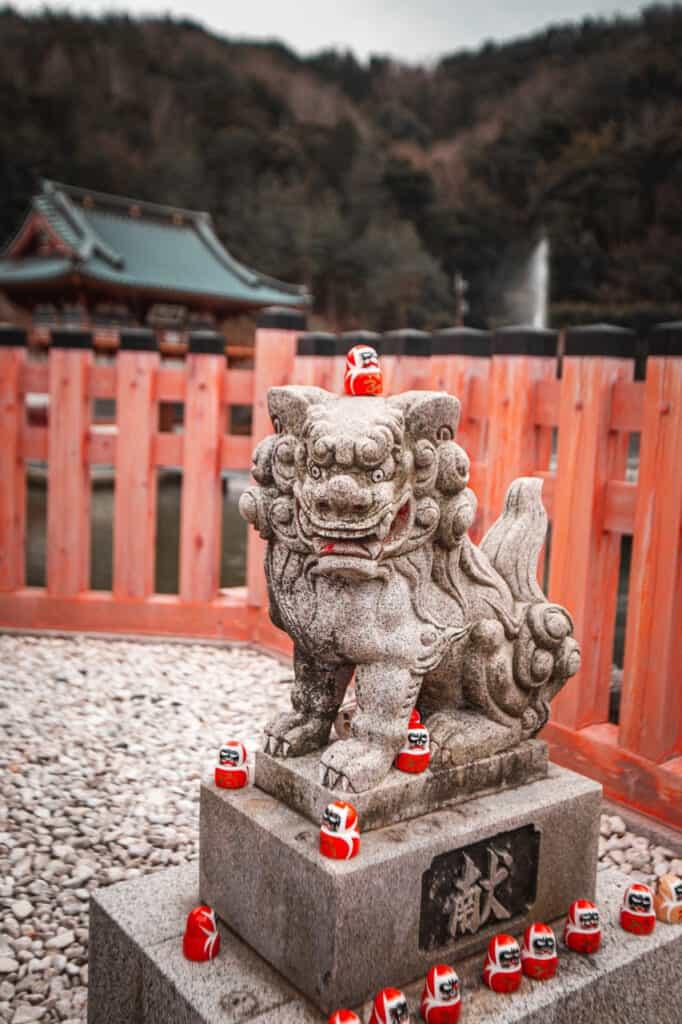 many daruma over a stone statue in Katsuo ji temple