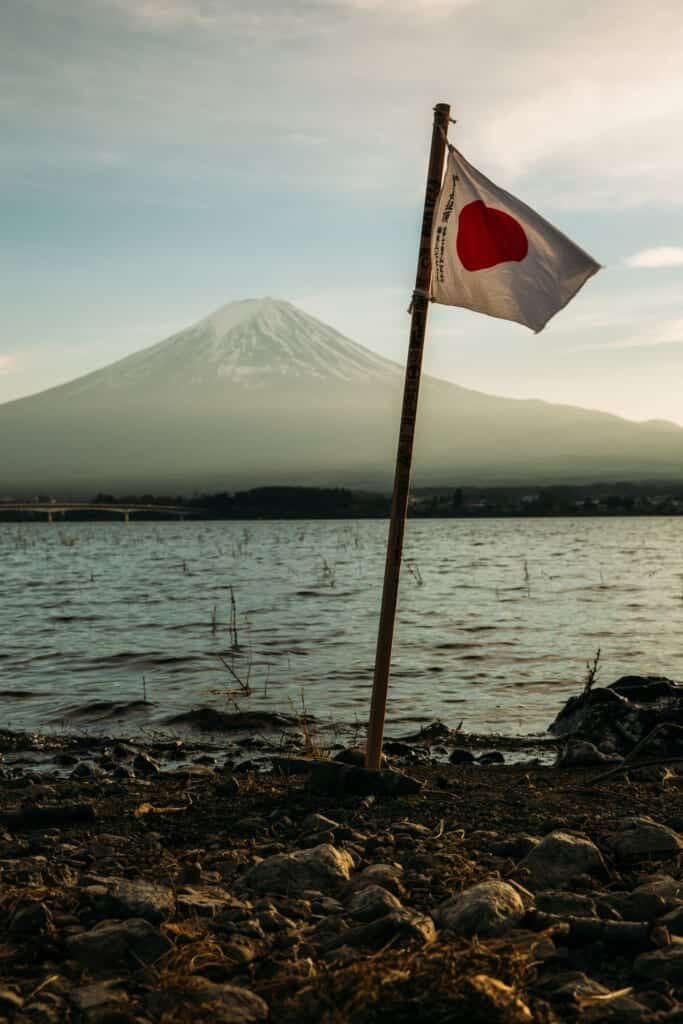 A japanese flag waving in front of Mount Fuji