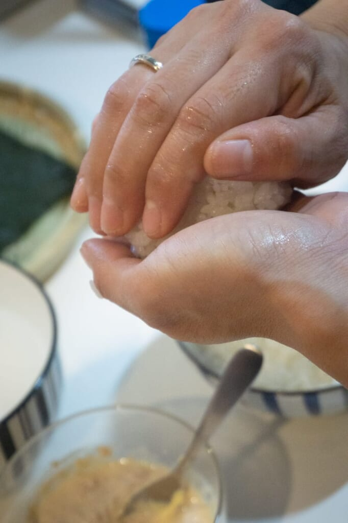 Give the deserved shape of the onigiri with your hands