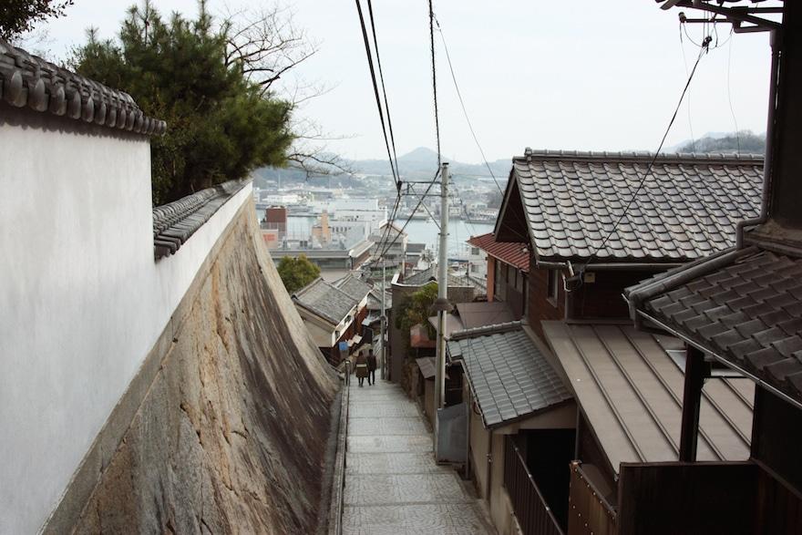 People walk down narrow Onomichi street
