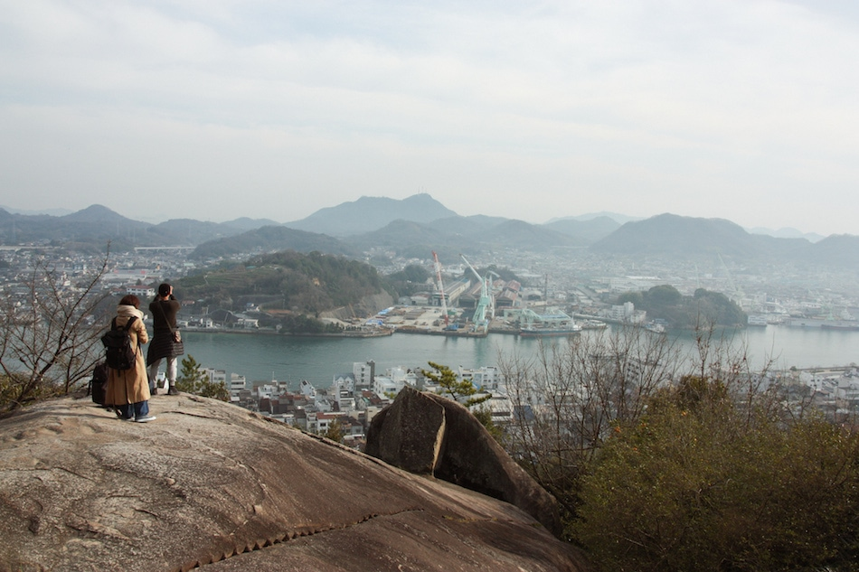 People standing on rock to take pictures of the Port town of Onomichi