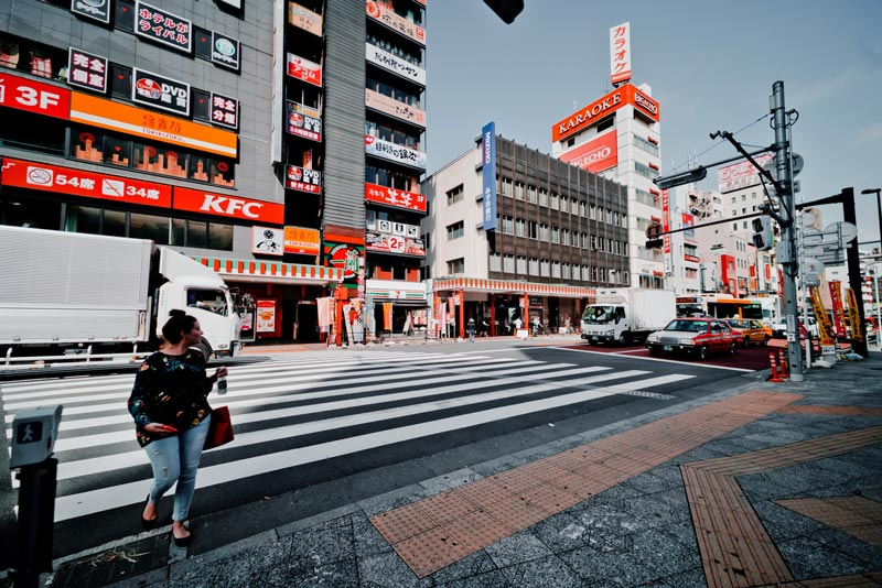 Girl crossing road with KFC in the background in Tokyo