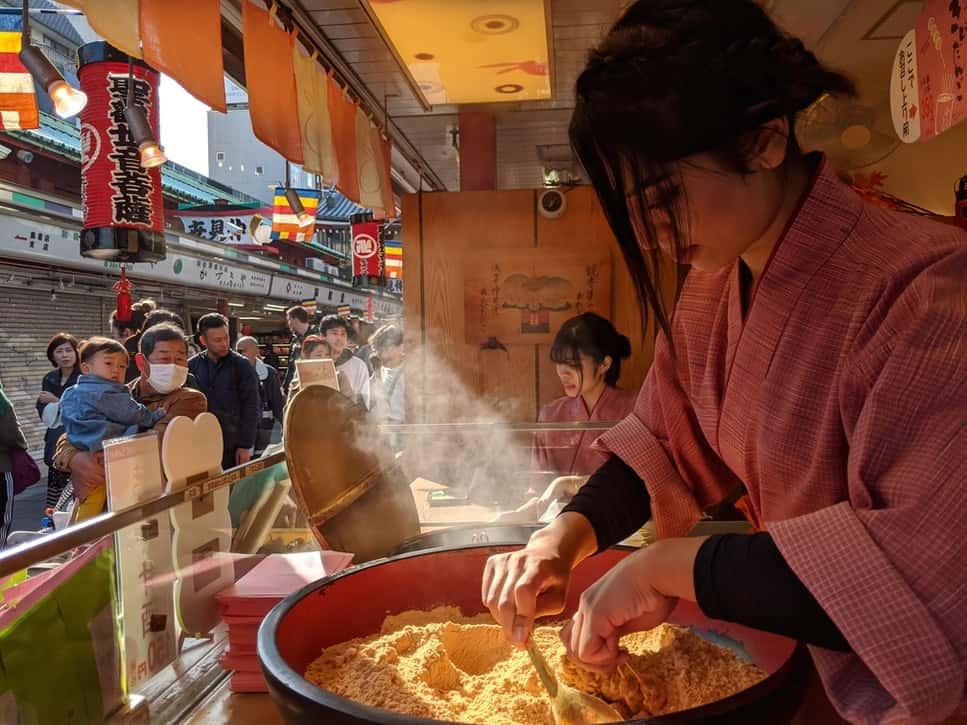 A girl cooking kibi dango in Asakusa, Tokyo