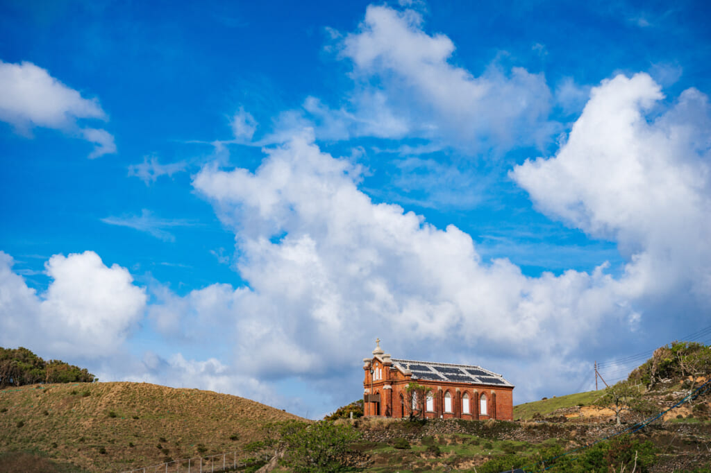 Former Nokubi Church stands on a hill with blue sky and big clouds
