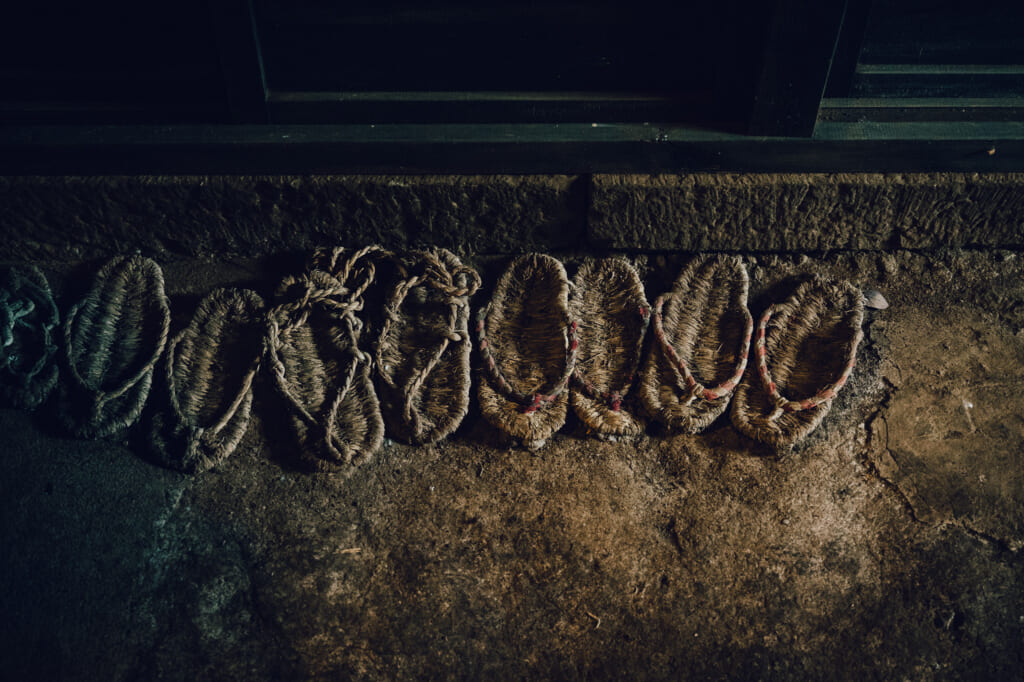 Old straw sandals on a dirt floor of a house on Nozaki Island in Japan