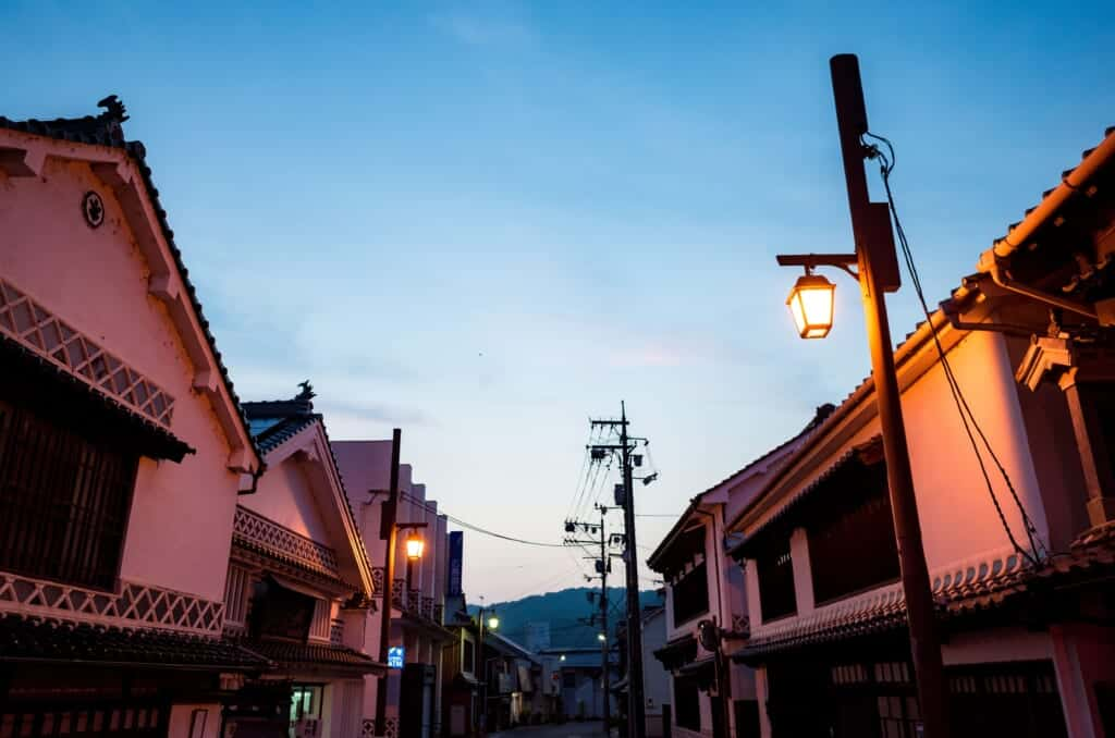 Street lined with Japanese traditional white-walled houses at dusk in Joge