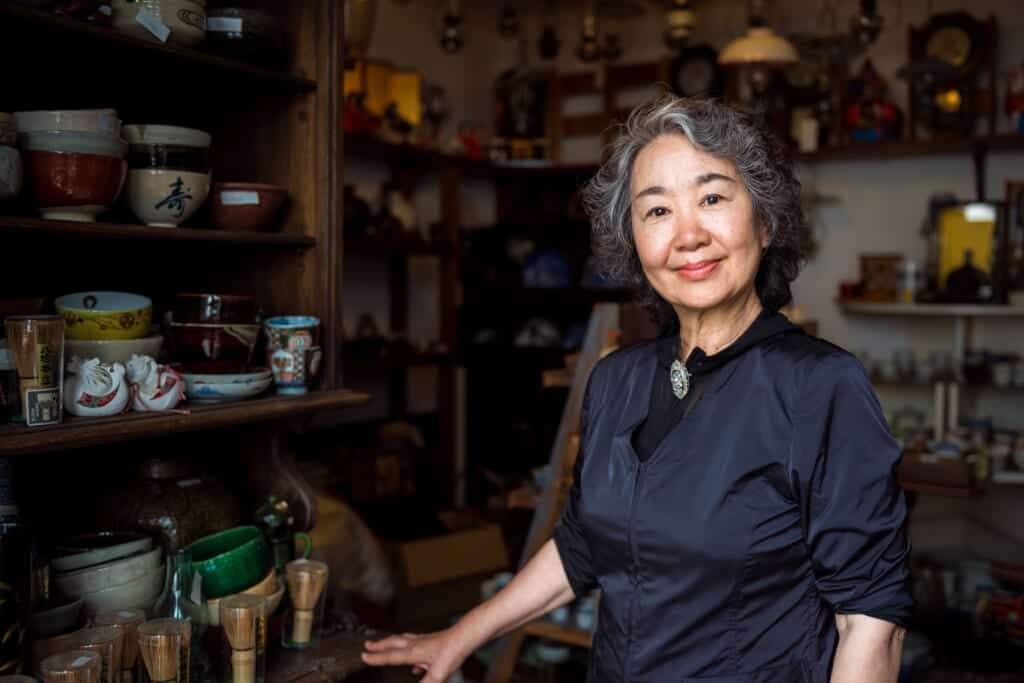 Smiling Japanese woman standing in her antiques shop in Joge town