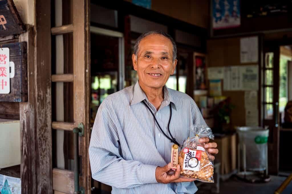 Japanese man holding senbei (Japanese rice crackers)