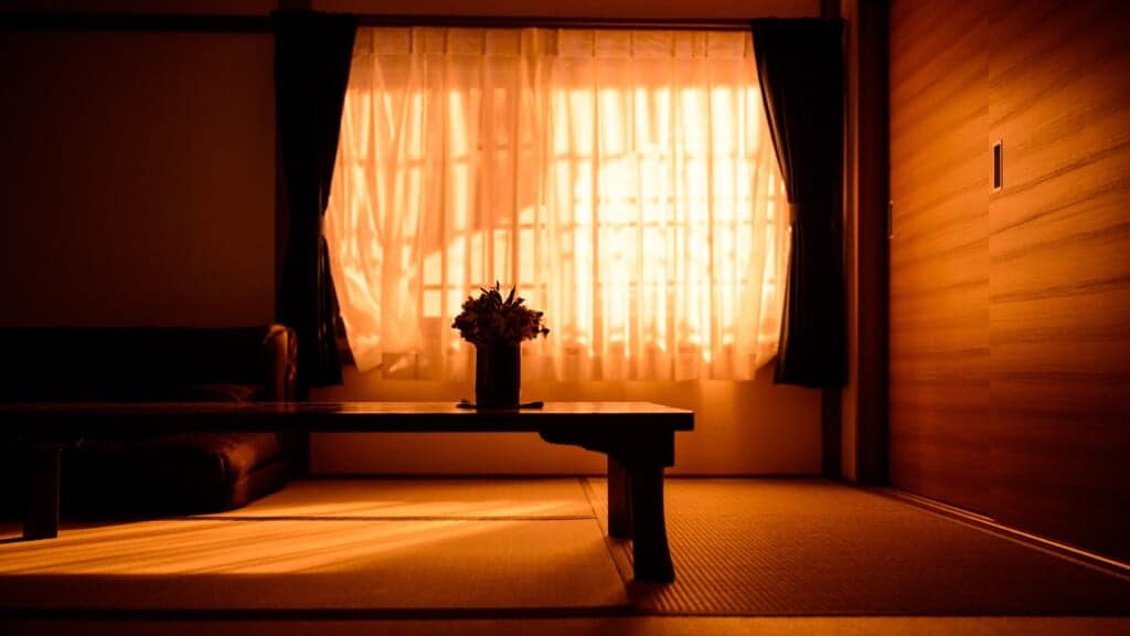 Inside a tatami room, in the orange light of the sunset