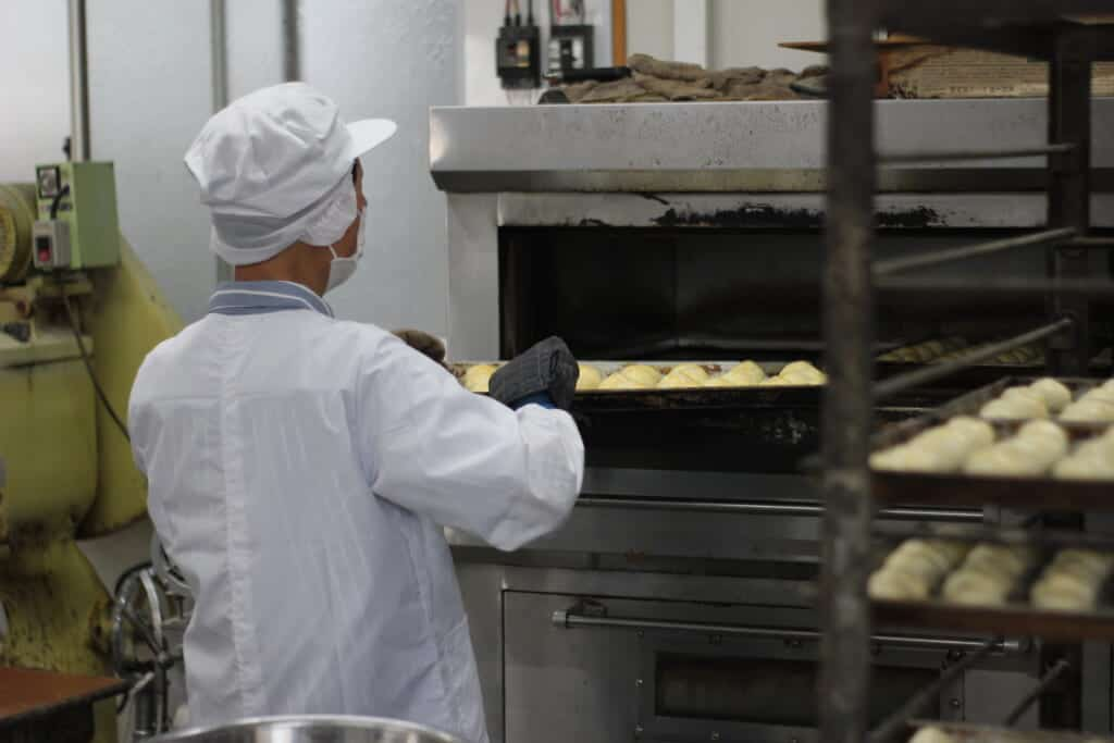 A man putting a tray full of Japanese pastries in an over