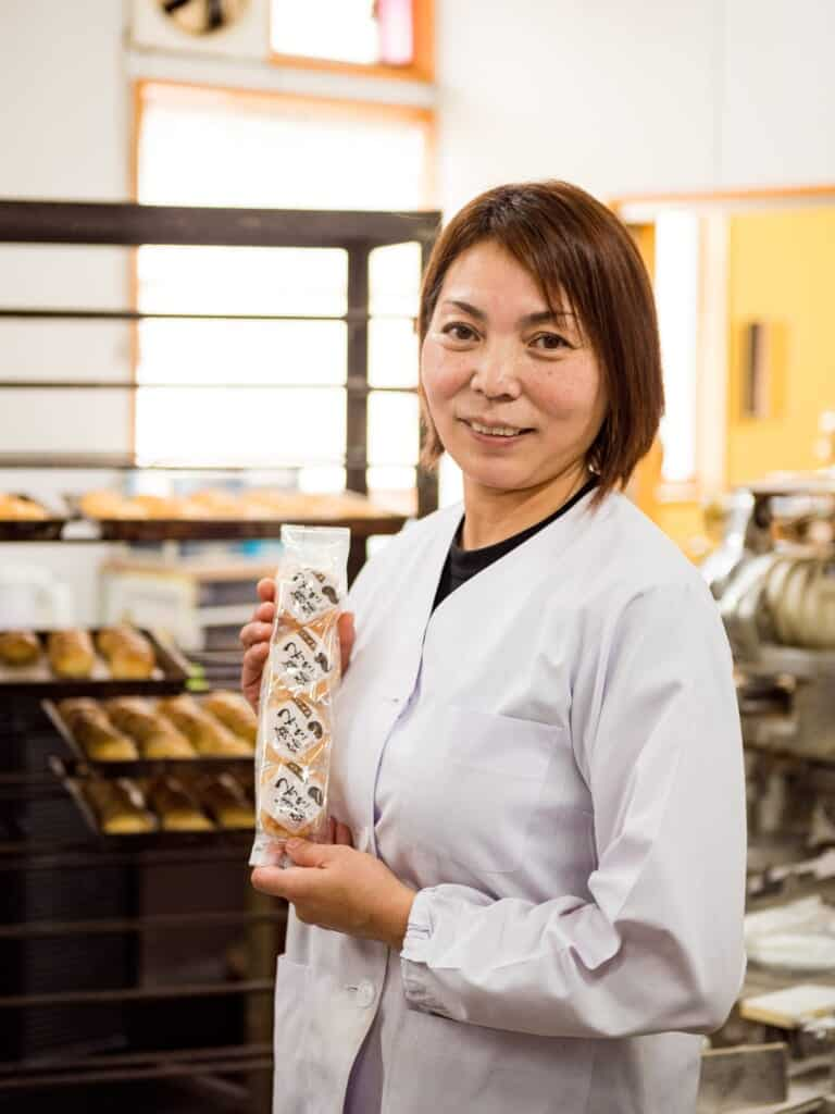 A Japanese woman showing a packet of fresh manju