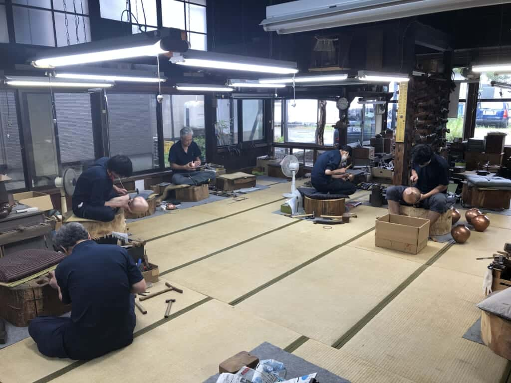 Japanese craftsmen crafting metal tea pots in a traditional tatami room.