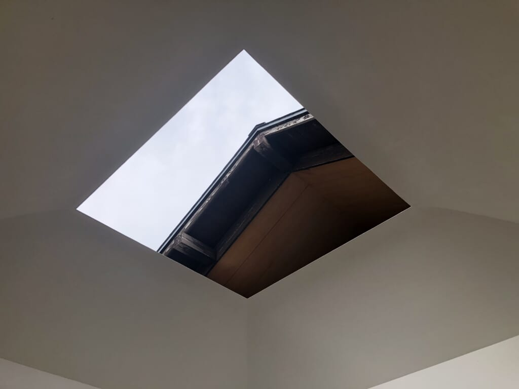 The hole in the roof of James Turrell's House of Light showing the sky and part of the traditional Japanese building
