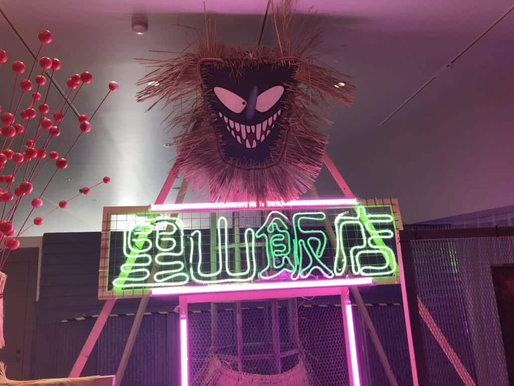 An artwork showing a pink frightening character and a green neon sign