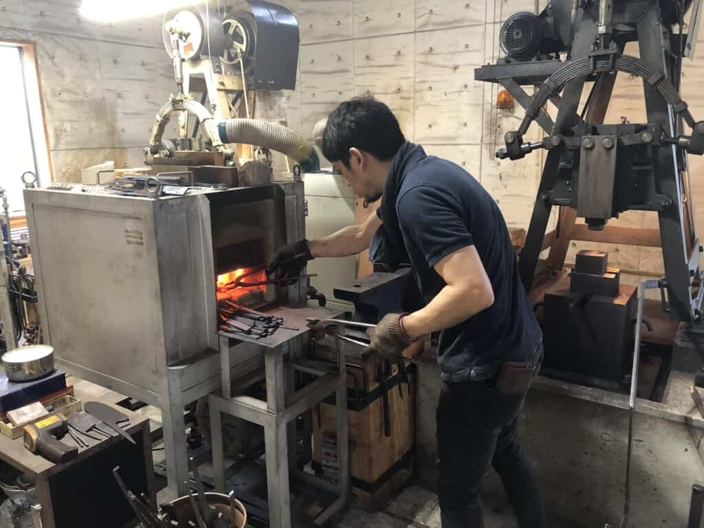 A Japanese blacksmith working to forge knifes.