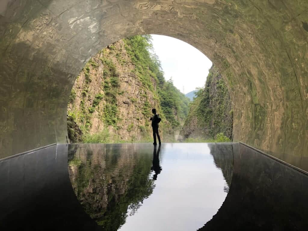 Someone standing in the Tunnel of Light, with reflexion on the water ground, Niigata
