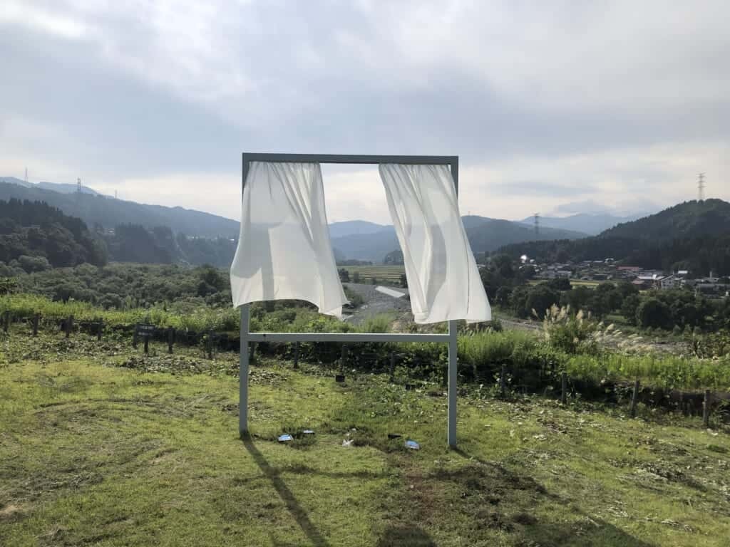 A so-called window in the middle of Japanese countryside, with white curtains moving with the wind. Artwork