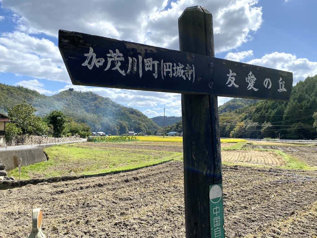A sign points to Kamogawacho in front of agricultural fields in Okayama