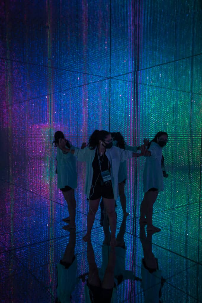 woman surrounded by rainbow illumination at teamLab Planets in Tokyo