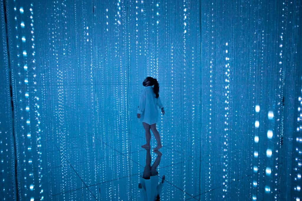 woman wandering around blue light crystals at teamLab Planets in Tokyo