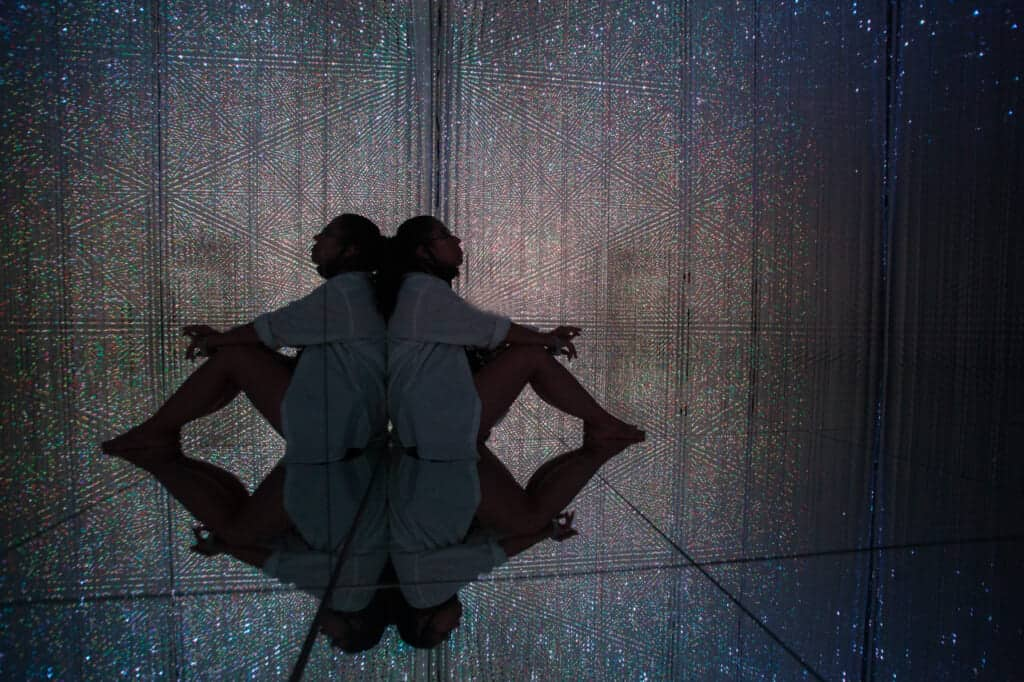 woman sitting in the mirrored floor surrounded by crystals of light at teamLab Planets in Tokyo