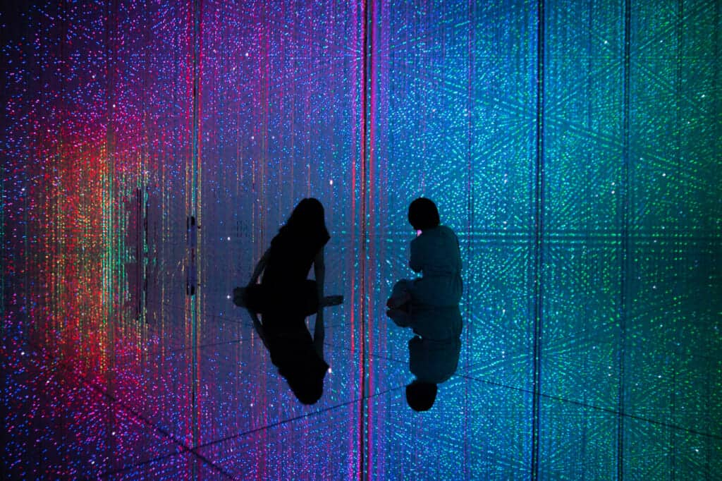 two women sitting in the mirrored floor at teamLab Planets in Tokyo