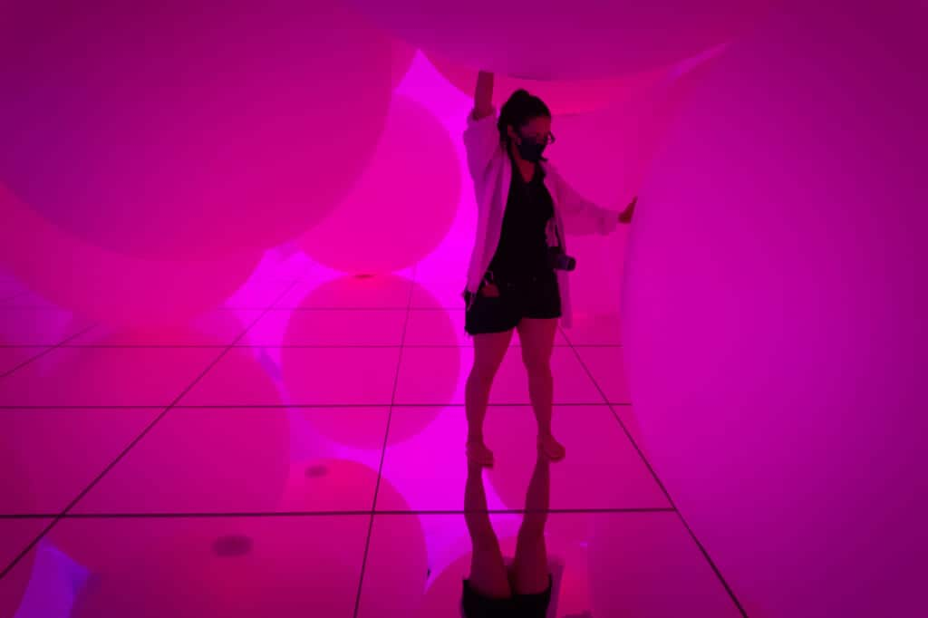 woman touching pink spheres of light at teamLab Planets in Tokyo