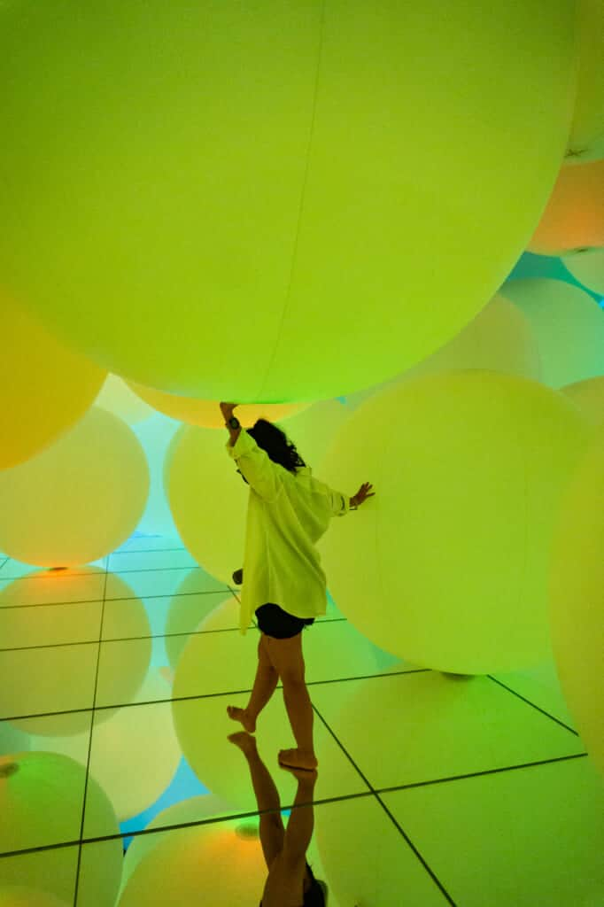 woman wandering around yellow spheres of light at teamLab Planets in Tokyo