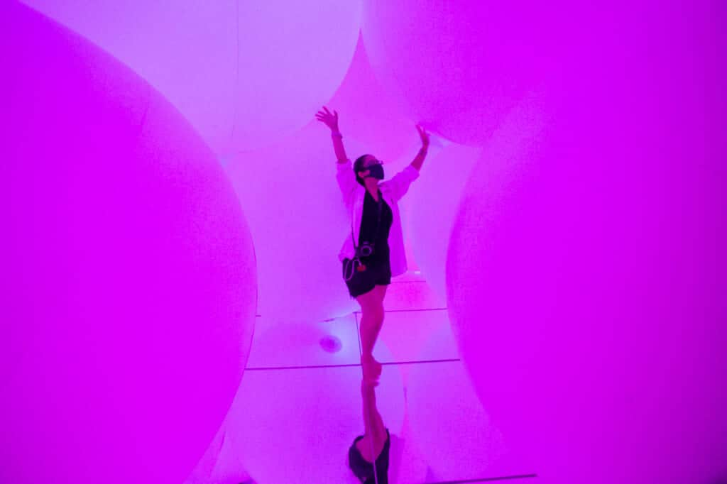 woman trying to touch the purple spheres of light