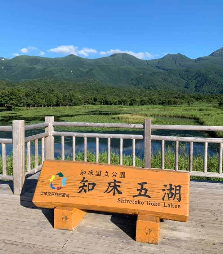 Signboard and overview on the Five Lakes landscape, mountains in the background
