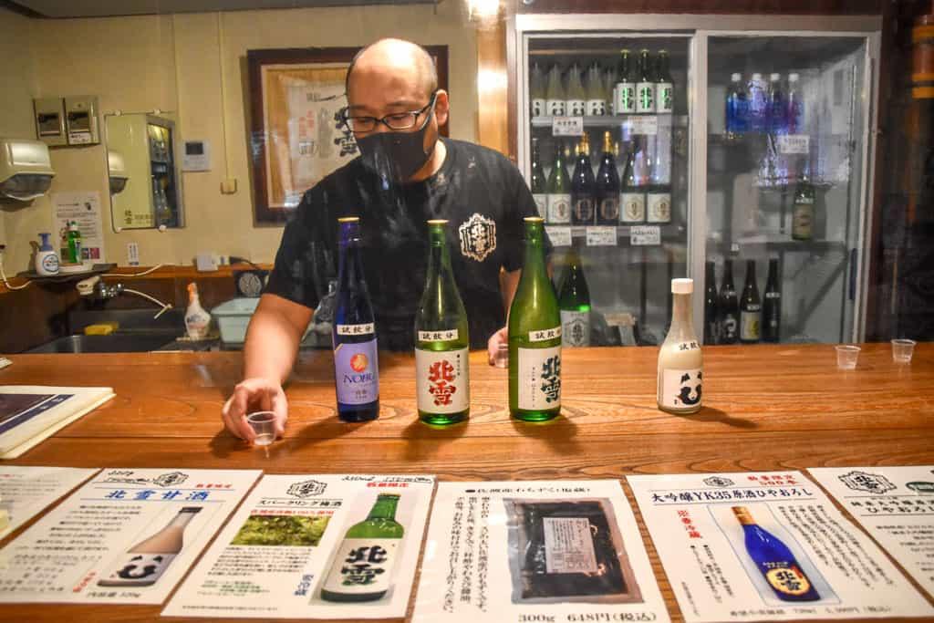 masked man serves sake on Sado Island in Niigata