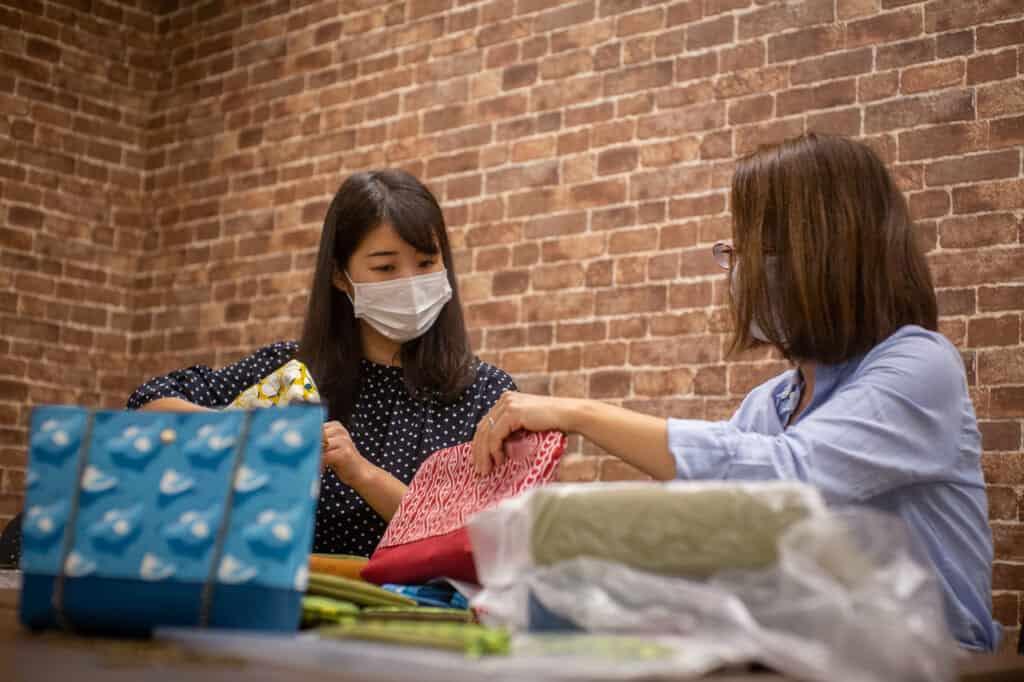 MinaHomi and Yurubia checking their Japanese textiles