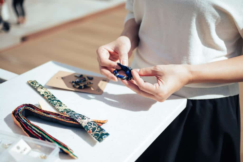 woman assembles earrings from recycled obi