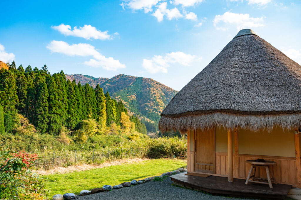 Mountain view with traditional Japanese thatched roof house in Miyama