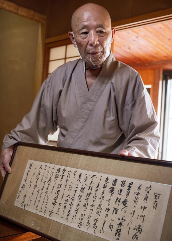 Buddhist Priest holds Japanese letter written in kanji in usuki, Oita, Kyushu