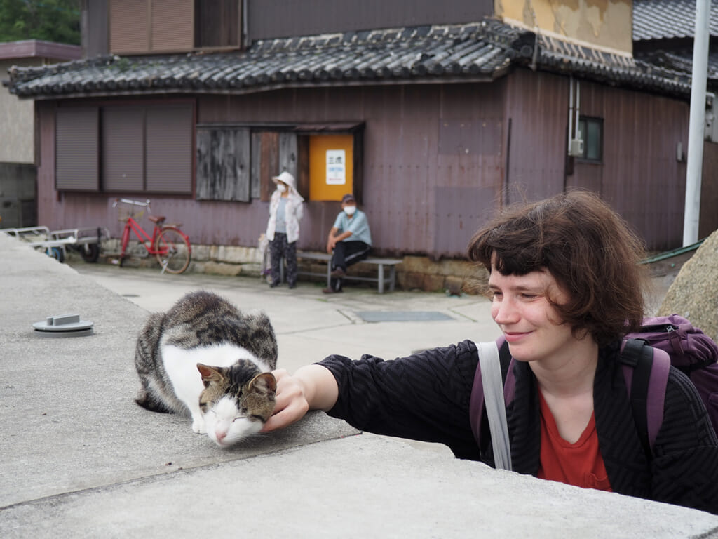 Clementina stroking a cat on Manabeshima, a cat Island in Japan