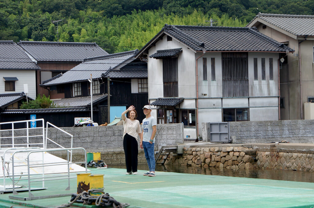 Two local residents waving from Manabeshima, a cat island in Japan