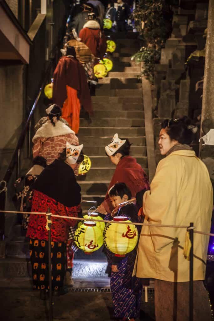 foxes climbing the stairs of Oji Inari Jinja