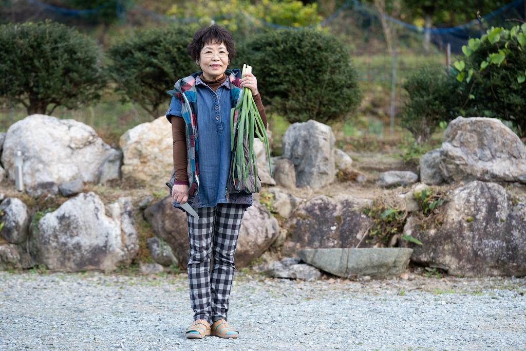 Mrs. Ogura holds fresh spring onions in front of the garden