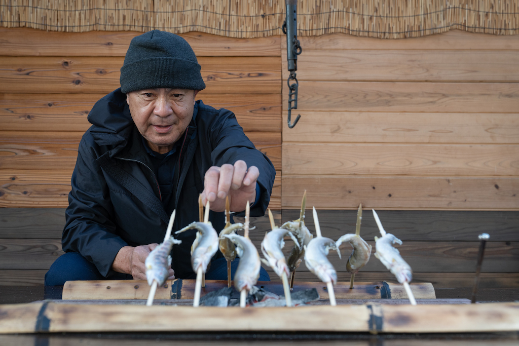 Mr. Ogura grills skewered Ayu fish over charcoal
