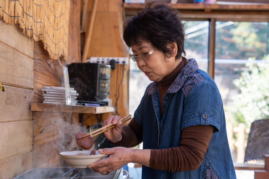 Mrs. Ogura prepares food in the kitchen