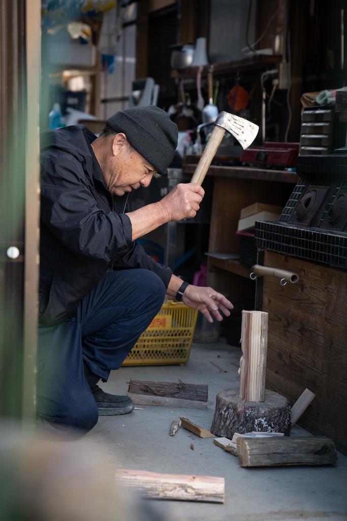 Mr. Ogura chops wood with an axe