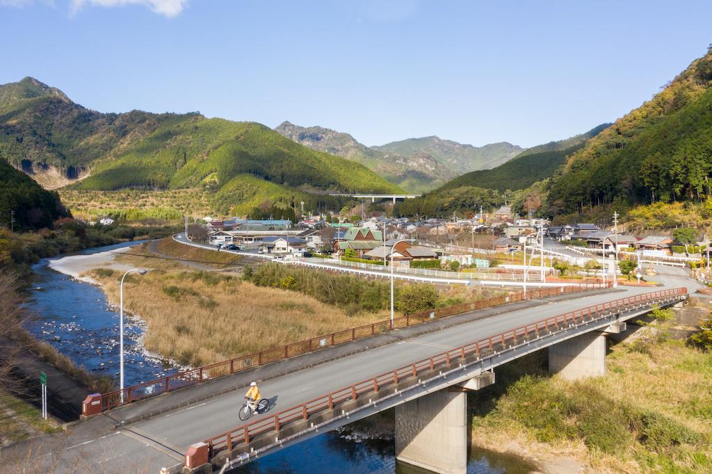 Cycling across a bridge over a river in the mountains of Kumano Kodo
