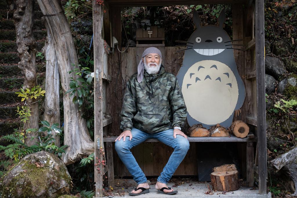 Mountain hermit sitting on bench next to Totoro