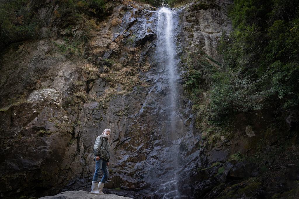 Mountain hermit under waterfall