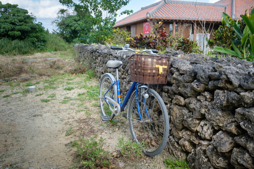 a bicycle in a stone wall in taketomi island